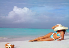 Woman on the beach. Attractive woman in hat lying on the beach Stock Photography
