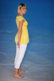 Woman on beach. A woman in a yellow babydoll standing on a beach in the twilight Stock Photo