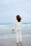 Woman on beach against sea and sky. Stock Photo