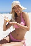 Woman on the beach applying sun block solar cream. Royalty Free Stock Photography