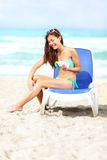 Woman on beach applying sunscreen lotion Royalty Free Stock Image