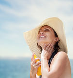 A woman on the beach applying suntan lotion Royalty Free Stock Photography