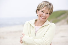 Woman at the beach with arms crossed smiling Stock Image