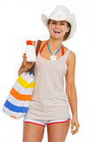 Woman with beach bag showing sun screen creme Royalty Free Stock Image
