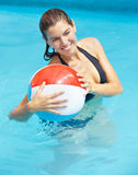 Woman with beach ball in pool Stock Photo