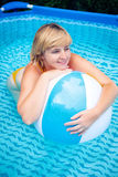 Woman with beach ball in swimming pool Royalty Free Stock Photography