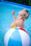 Woman with beach ball in swimming pool Stock Photo