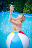 Woman with beach ball in swimming pool Stock Images