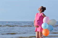 Woman on beach with balloons Royalty Free Stock Photo