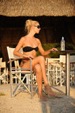 Woman in the beach bar. The pretty woman sitting in the beach bar with a bottle of water Stock Photography