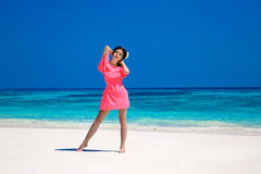 Woman on the beach. Beautiful slim girl model in red dress resti. Ng on exotic sea, tropocal seashore. Wellness. Healthy lifestyle. Travel Royalty Free Stock Photography