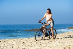 Woman on beach with bike