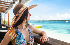 Woman in beach cafe enjoying ocean view in vacation Stock Image