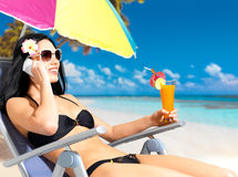 Woman on the beach calling by mobile phone Stock Photos