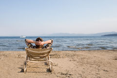 Woman in Beach Chair Looking Away at Horizon. Relaxed woman sitting in a chair at the beach with her hands clasped behind her head.  Looking at the horizon as a Stock Photo