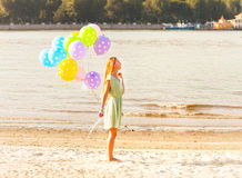 Woman on the beach with colored polka dots balloons Stock Photography