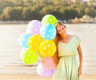 Woman on the beach with colored polka dots balloons Royalty Free Stock Image