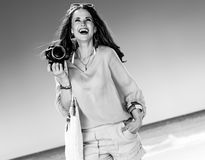 Woman on beach with digital SLR camera looking at copy space. Perfect summer. smiling young woman in shorts and yellow blouse with white beach bag on the beach Stock Images