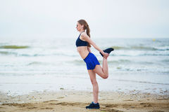 Woman on beach doing stretching exercise after a workout Stock Photography