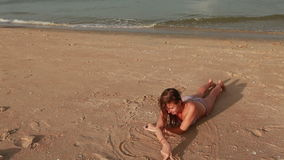 Woman on the beach drawing on sand stock video footage