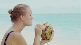 Woman on the beach drinking from coconut stock video