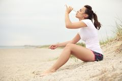 Woman at the Beach Drinking Water Royalty Free Stock Images