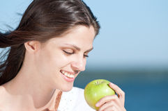 Woman on beach eating fruits Stock Photo
