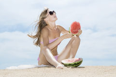 Woman at the beach and eating watermelon Stock Image