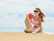 Woman on the beach and eating watermelon Stock Image