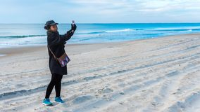 Woman on beach taking selfie with ocean behind her stock images