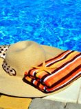 Woman beach hat, bright towel against swimming pool Stock Photo
