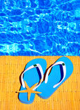 Woman beach hat, bright towel against swimming pool Stock Images