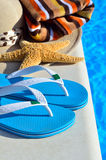 Woman beach hat, bright towel and blue flip-flops Stock Photography
