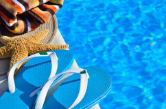 Woman beach hat, bright towel and blue flip-flops Stock Images