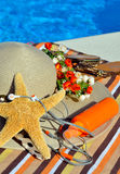 Woman beach hat, bright towel, headphones and starfish. Royalty Free Stock Photo