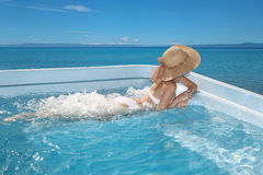 Woman in beach hat enjoying in jacuzzi, swimming pool on Tropica. L Resort. Exotic Greece Paradise. Travel, Tourism and Vacations Concept Stock Photos