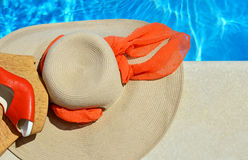 Woman beach hat and red sandals. Woman beach hat and red sandals on the pool background Royalty Free Stock Photos