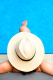 Woman with beach hat relaxing by the pool at exotic resort Royalty Free Stock Photo