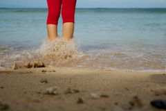 A woman in the beach heading to the sea. A woman standing in the beach heading to the sea Stock Photos