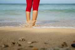 A woman in the beach heading to the sea. A woman standing in the beach heading to the sea Royalty Free Stock Images