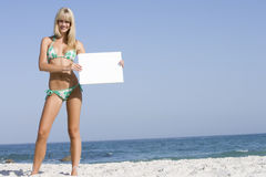 Woman on beach holding blank card Royalty Free Stock Photos