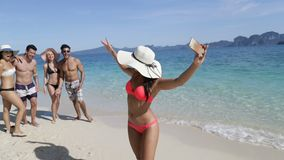 Woman On Beach Holding Cell Smart Phone Call People Group To Take Selfie Photo, Happy Smiling Young Tourists Group stock video