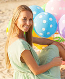 Woman on the beach holding colored polka dots balloons Stock Photo