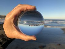 Woman at the beach holding a crystal ball royalty free stock photography