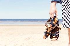 Woman on the beach holding her sandals at sunny summer day stock photos