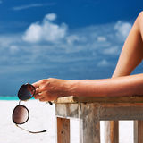 Woman at beach holding sunglasses Royalty Free Stock Image