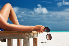 Woman at beach holding sunglasses Stock Photos