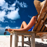 Woman at beach holding sunglasses Stock Photography