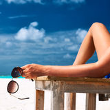 Woman at beach holding sunglasses Royalty Free Stock Photography