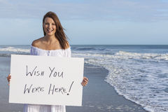 Woman on Beach Holding Wish You Were Here Card. Happy smiling beautiful girl young woman on sunny vacation beach holding white card saying Wish You Were Here Stock Photography